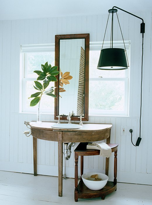 Darryl Carter designed country style bathroom with demilune vanity and beadboard walls