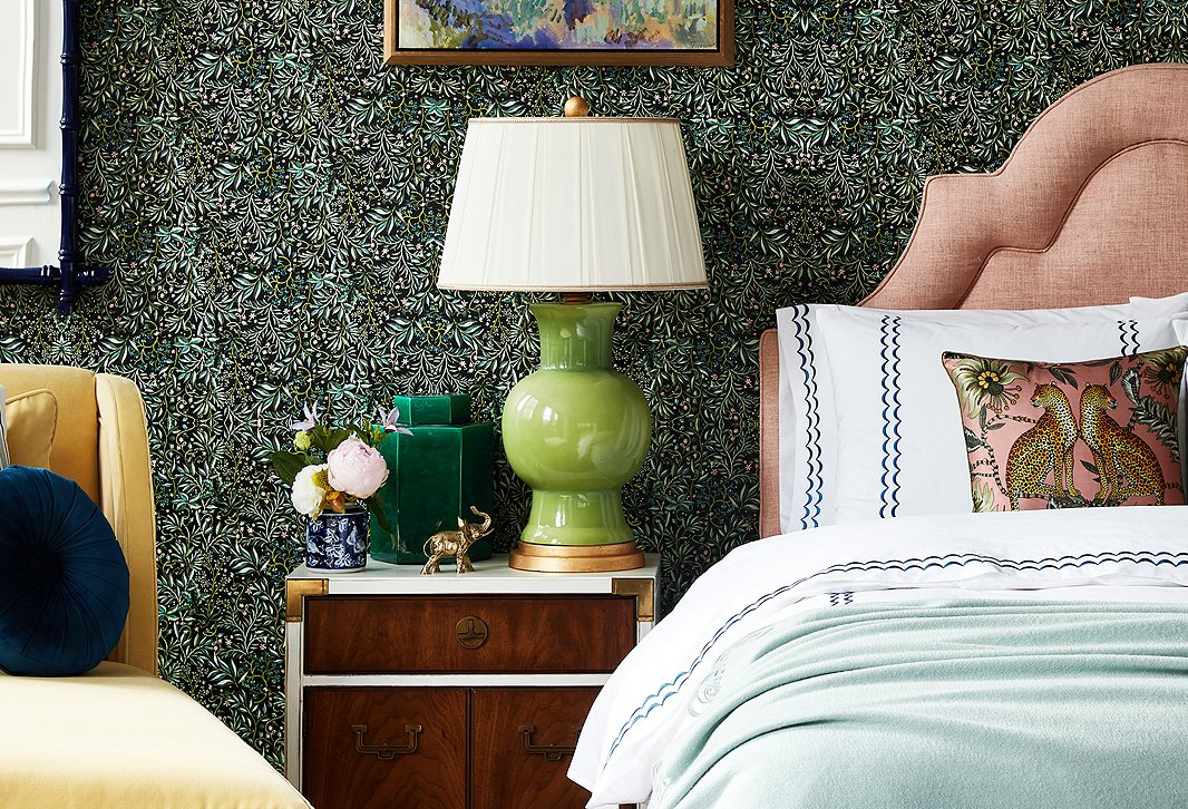 The darker hues and dense motif of theVikki Chu Black Forest Wallpaper tie together the disparate room elements in a way that plain pale walls never could. Furnishings above includeRoslin Chaise in Canary Velvet,Eileen Round Pillow in Indigo,Vintage Campaign-Style Nightstand,Emmy Table Lamp in Green/Gold, andKennedy Bed in Blush.