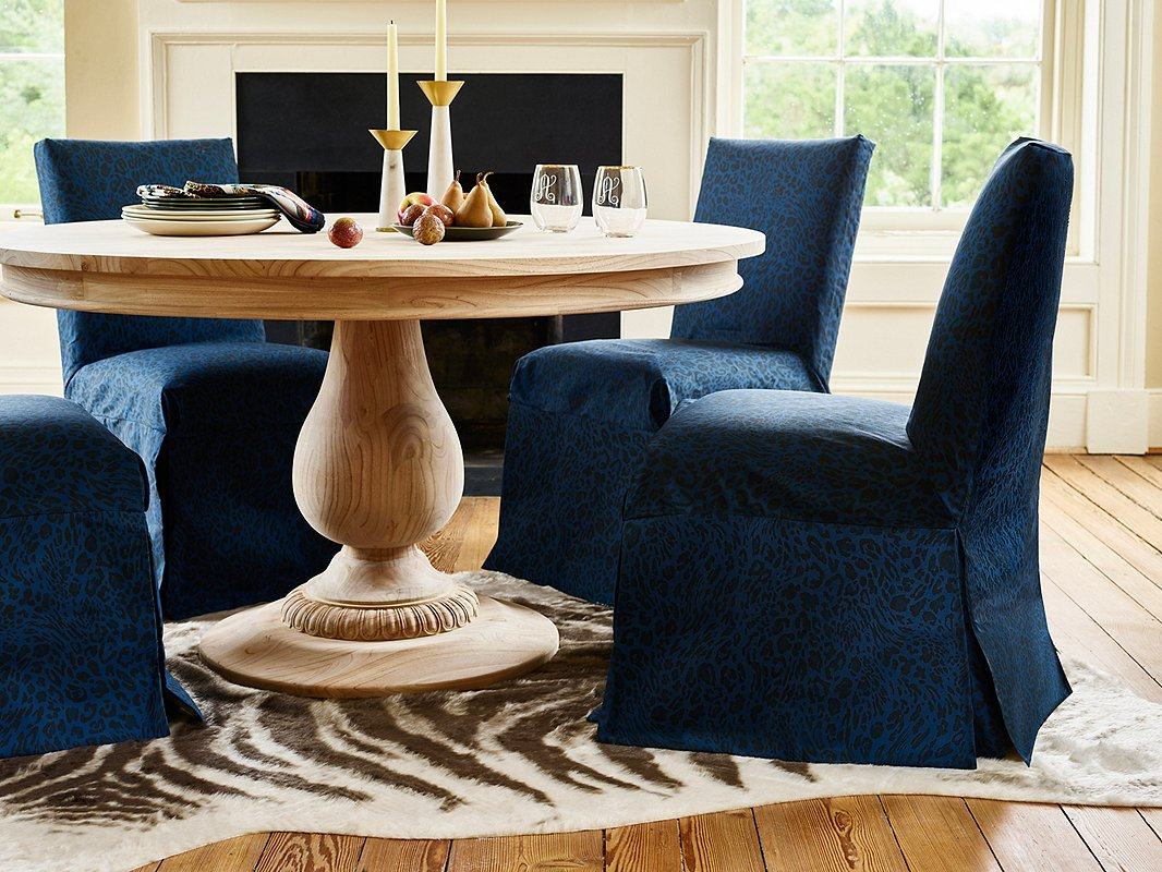 A nature-inspired palette doesn't have to mean all earth tones. The deep blues of the evening sky add organic drama to a room. Case in point: these Owen Slipcover Chairs. The unfinished wood of the Charlotte Round Dining Table both contrasts with and complements its refined shape. Find the marble-and-steel candlesticks here.
