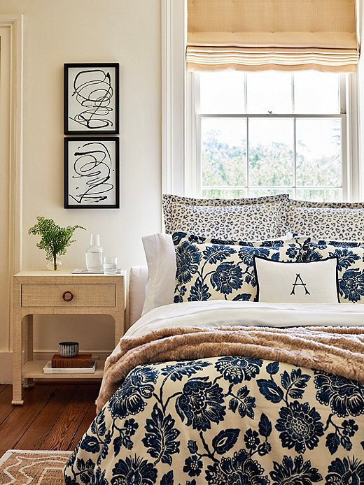 The raffia-covered nightstand and the faux-fur throw bring a literal touch of the outdoors into this bedroom. The Carrie Leopard Shams and the floral duvet cover introduce natural motifs; the Harper Monogram Boudoir Sham gives the room a Southern accent.