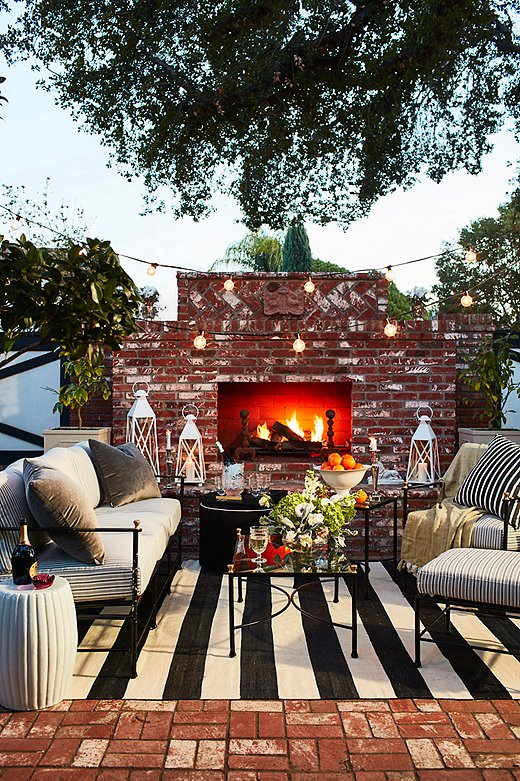 Decorate your outdoor space as you would any other part of your home. Don't forget the accessories. In this case, we stuck to a dark color palette and layered in rugs, blankets, pillows, lanterns, and string lights. Fall flowers also add a nice touch to any space.