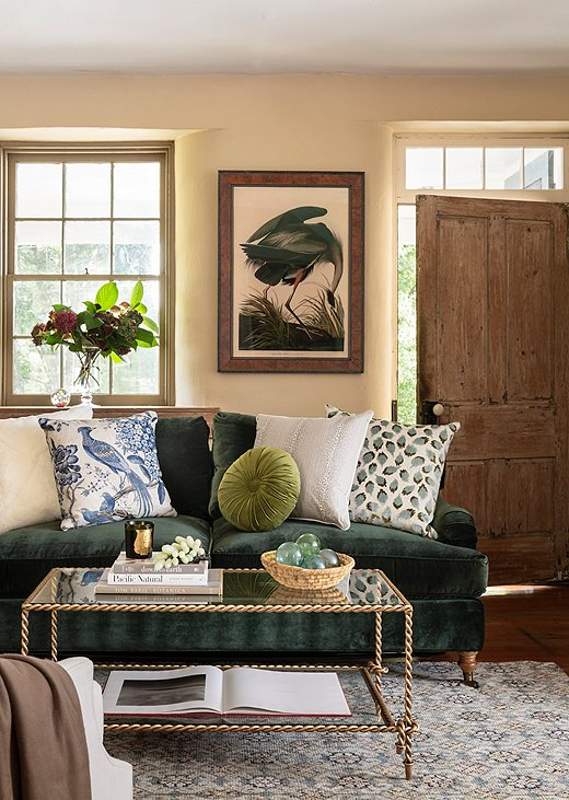 A two-seater velvet sofa with performance fabric sings in a small sitting room. Fun pillows (including our exclusive round pillow) add some much needed texture, while a streamlined coffee table frees up visual real estate. Photo by Helen Norman.