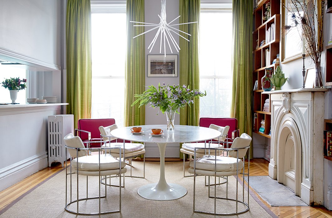 "The dining room/library is a ""hub"" of the family home. That calls for durable pieces such as a sisal rug and a marble-top Saarinen Tulip table that works for dinnertime, homework, reading, and more. The chartreuse curtains (also in the living room) are from a textile not-for-profit in Southeast Asia."