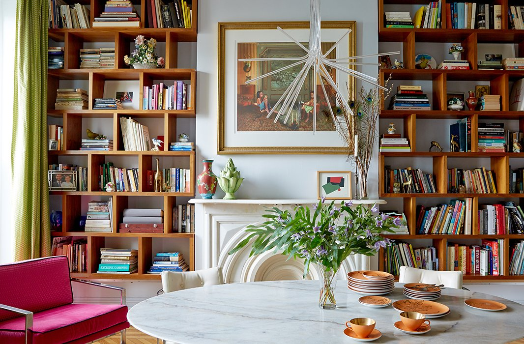 "Ever a fan of juxtaposition, Fawn loves how the contemporary light fixture sprouts ""like a flower"" from the ceilings's decorative molding. The custom-built shelving provides much-needed storage in the home, which was built more than a century ago. New York artist and friend Meghan Boody gifted the piece above the mantel."
