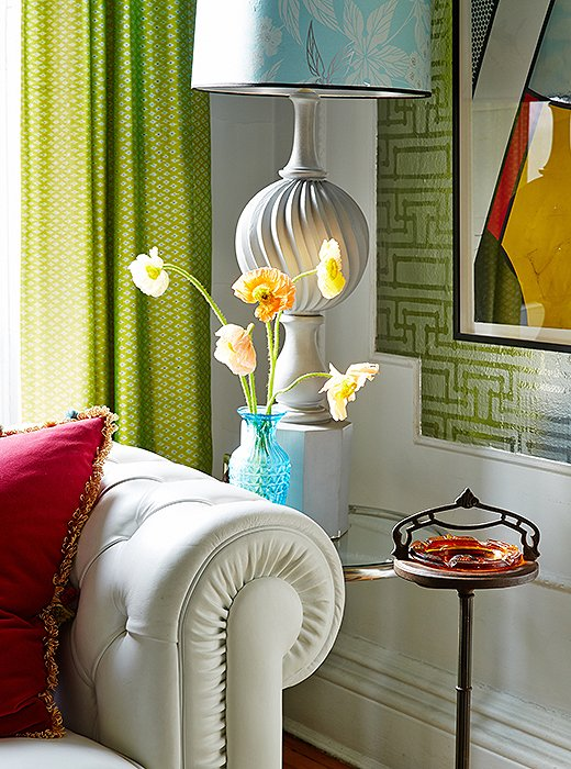 "The lamps show Fawn's high-low approach. ""The bases were $50, while the custom shades were pricey."" The metallic Florence Broadhurst wallpaper helps to ""bring light into the room."" The Roy Lichtenstein artwork is actually a wallpaper panel that Robert Stern gave Fawn."