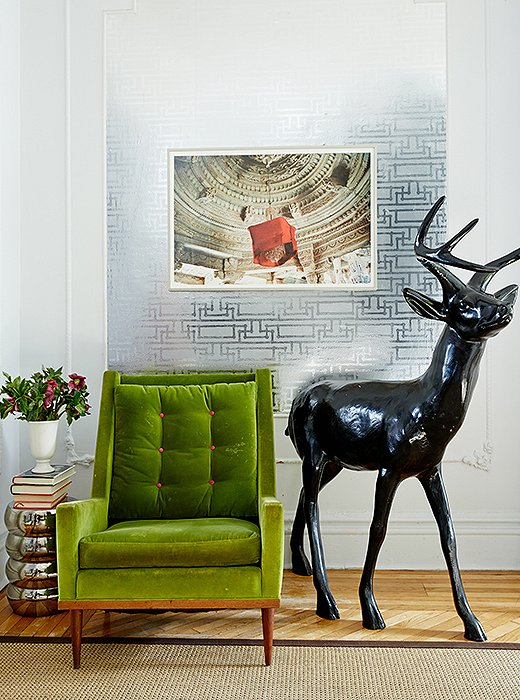 "A midcentury chair is covered in a vibrant green velvet. The deer sculpture is a flower-market find that Fawn lacquered in black, which she often uses ""to ground a space that has pops of color."" The photograph is by Jonathan Ball."