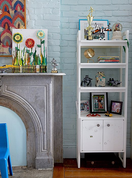 "The trophies, artwork, and action figures that adorn the shelving and mantel are the handiwork of Fawn's 7- and 10-year-old boys. ""Remember, kids need space for their own things."""
