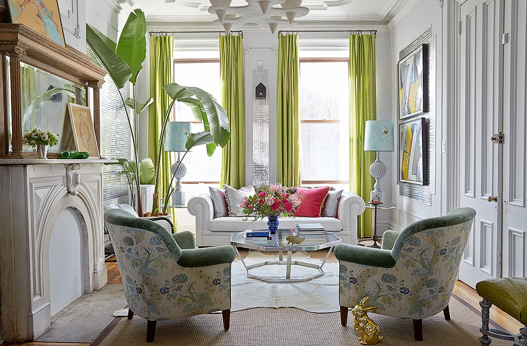 Trim in a rich, warm green velvet ensures that the floral pattern of the chairs feels appropriate even in winter. As well as contributing a tropical note, the towering plant draws the eye upward to the elaborate moldings. Photo by Tony Vu; design by Fawn Galli.