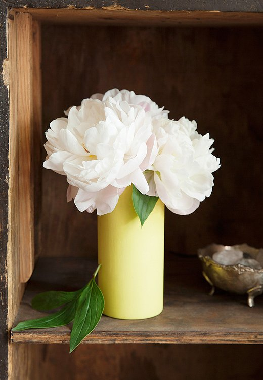 For next to the bed, think simple and sweet. Porcaro tucked a trio of peony blooms, and nothing else, into a low yellow vase for a result that's calming, fragrant, and just plain lovely—perfect to wake up to.