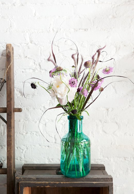 A transparent container, like this blue-grass vase, evokes a casual, seaside mood. Set this bouquet in an entry as a cheerful welcome for guests.