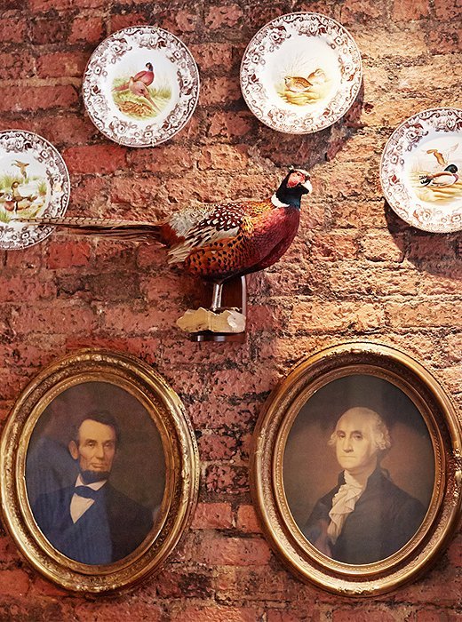 Spode plates and a stuffed pheasant share a wall with George and Abe.