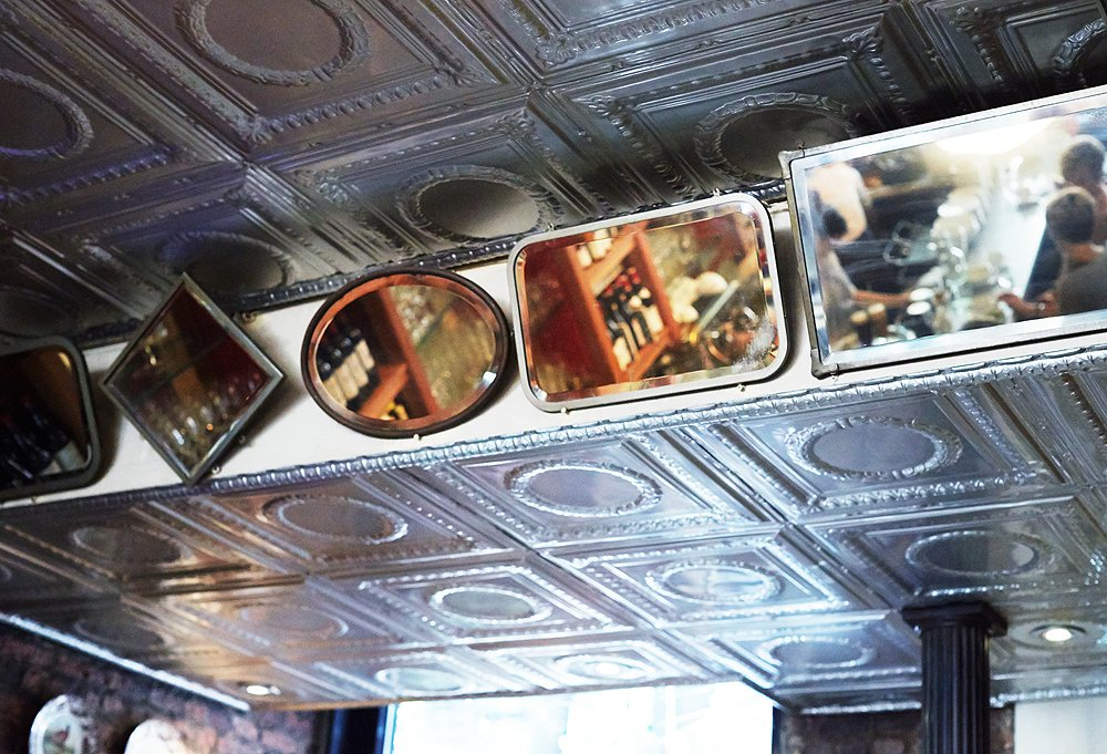 The bistro's collection of antique mirrors highlights the tin ceilings.