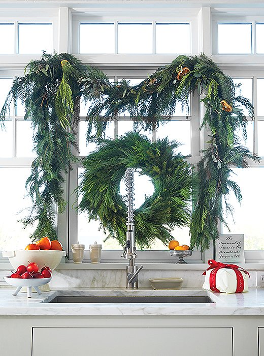 A cedar wreath and swags frame a gorgeous sink; bowls of fruit and a present or two underline the mood.