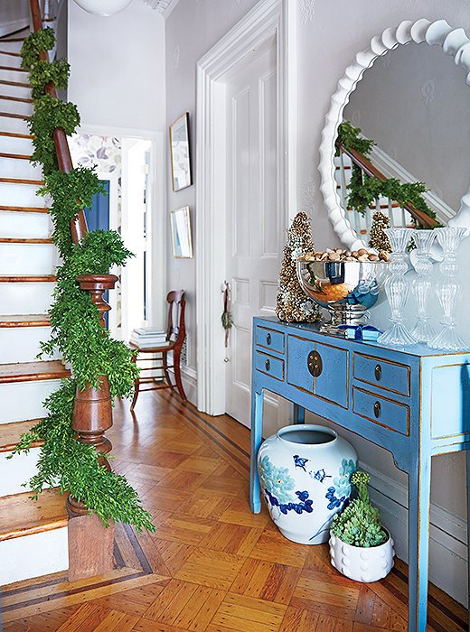 Curate your entryway with color. Here, the green garland sets off the space's gorgeous shades of blue.