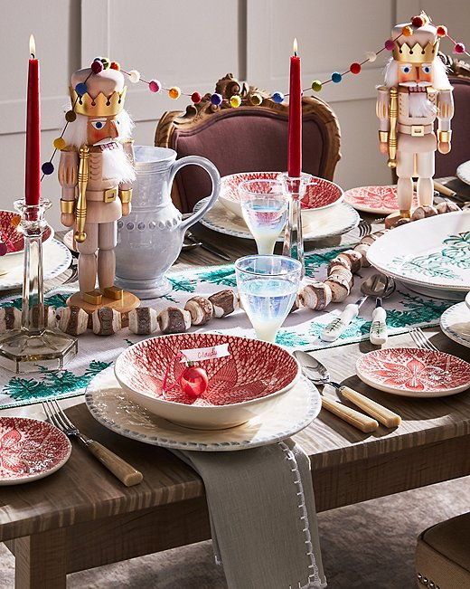 Set a playful scene with wares from Vietri's holiday collection and nutcrackers draped in whimsical garlands.