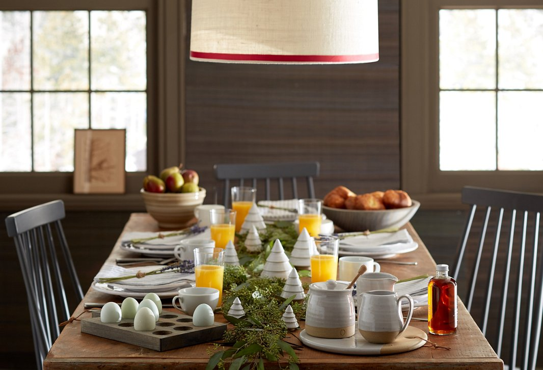 Farmhouse Pottery's wares are a simple yet stunning way to set the table for any season. Use a garland of fresh greenery as the centerpiece to bring home the holiday look.