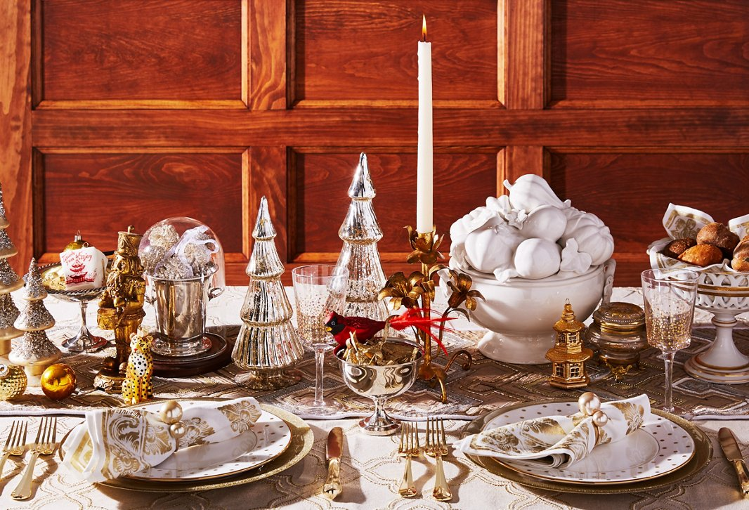 Glass Christmas trees, gold plates and flatware, and a beaded runner make for a decidedly decadent tablescape.