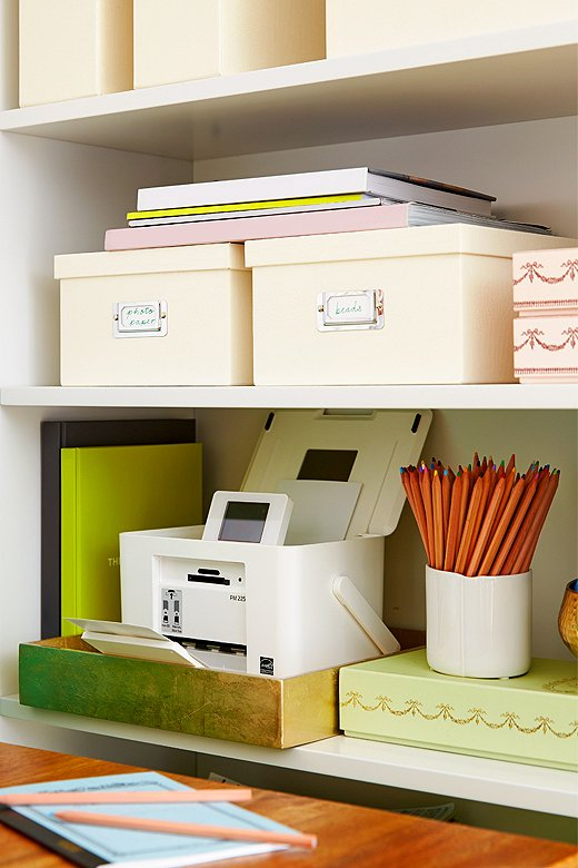 Dress up neutral storage boxes on shelves by mixing in some pretty repurposed candy boxes, metallic bowls, and a few colorful books.