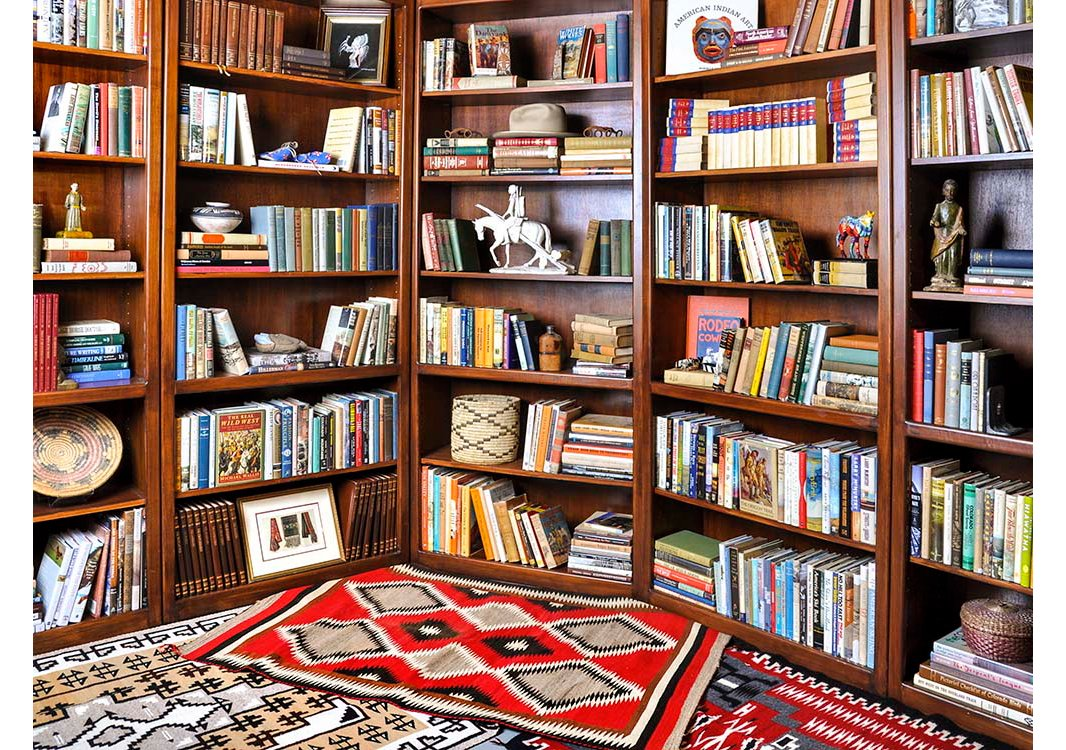 Vintage leather-bound sets, novels, and a collection of baskets and statuettes fill the shelves of this eclectic library.