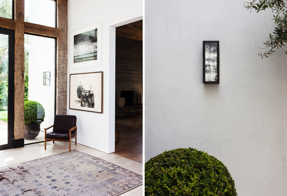 A vintage Chinese rug and a Danish chair Kayne's husband owned when they first met are simple comforts warming up the expansive foyer. Mercury-glass exterior lighting is simple yet stunning.