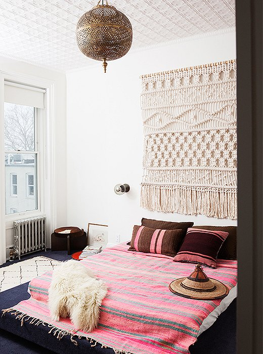 Key elements define the master bedroom: A built-in carpeted platform bed, and the rope wall hanging by Sally England is the first piece Julia ever commissioned.