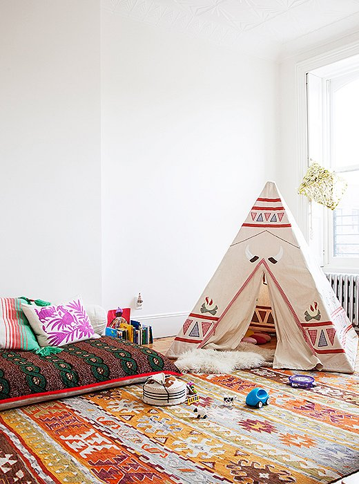 Alongside a mini yurt from Mongolia and an Aztec tepee, an African waxed-cloth floor pillow serves as a sleepover spot and a place to read. The brick-red-and-orange palette is meant to evoke a 1940s vibe.