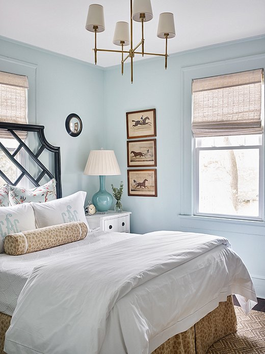 Benjamin Moore's Palladian Blue sets the serene stage forthe main bedroom. Natural tones play on the sunlit room to bring warmth. The Camille Chandelier from Visual Comfort adds a touch of glam.