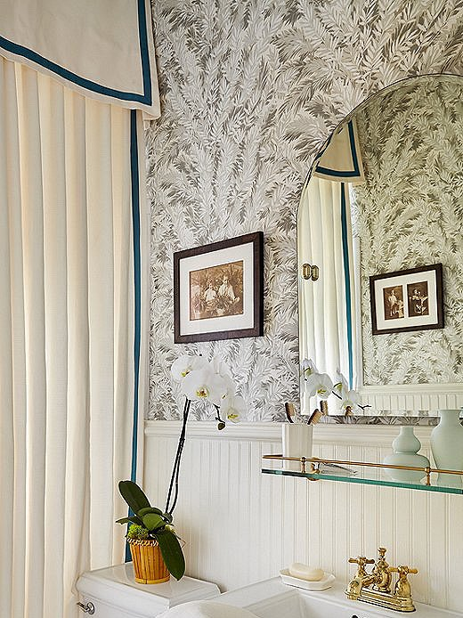 The pop of jewel tone on the custom shower curtain brings depth to the bungalow bathroom. The walls are covered in the iconic Florencecourt Wallpaper from Cole & Son.