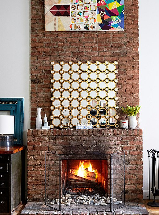 """We love sitting by the fire, especially in the winter,"" says Lisa. On the mantel is an Art Deco-inspired mirrored piece Lisa bought years ago from One Kings Lane."