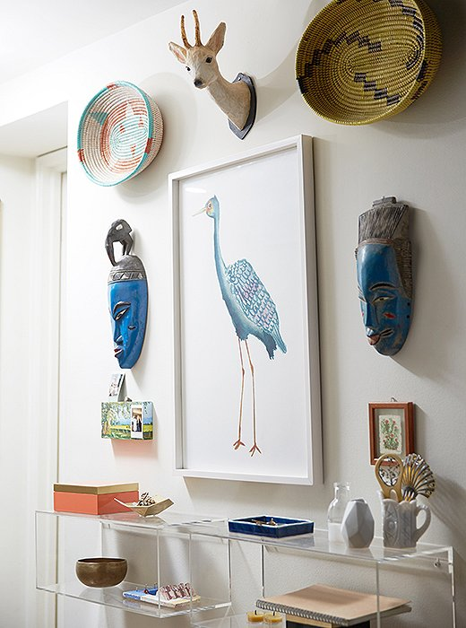 The entryway is decorated with pieces collected from their travels, including a papier-mâché deer head, African masks, and a Tibetan singing bowl.