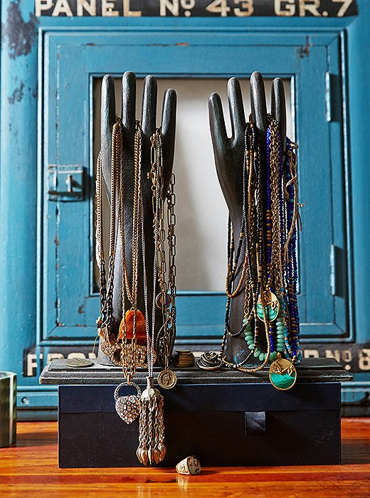 More necklaces are displayed on a pair of antique Indian wooden glove-making molds that Lisa picked up while traveling in Nepal. Behind them is a 1930s electric panel originally from the Con Edison building in New York City.