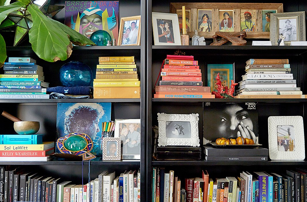 "Their ""happy bookshelf,"" as Lisa likes to call it, is artfully arranged with color-coded tomes, favorite photos, old records, and pieces from their travels. ""The colored markers I use to sketch and draw are on display too,"" says Lisa. The framed piece on the top right shelf features several Native American portraits; Lisa got it in Montana when she was working there on a cattle ranch."