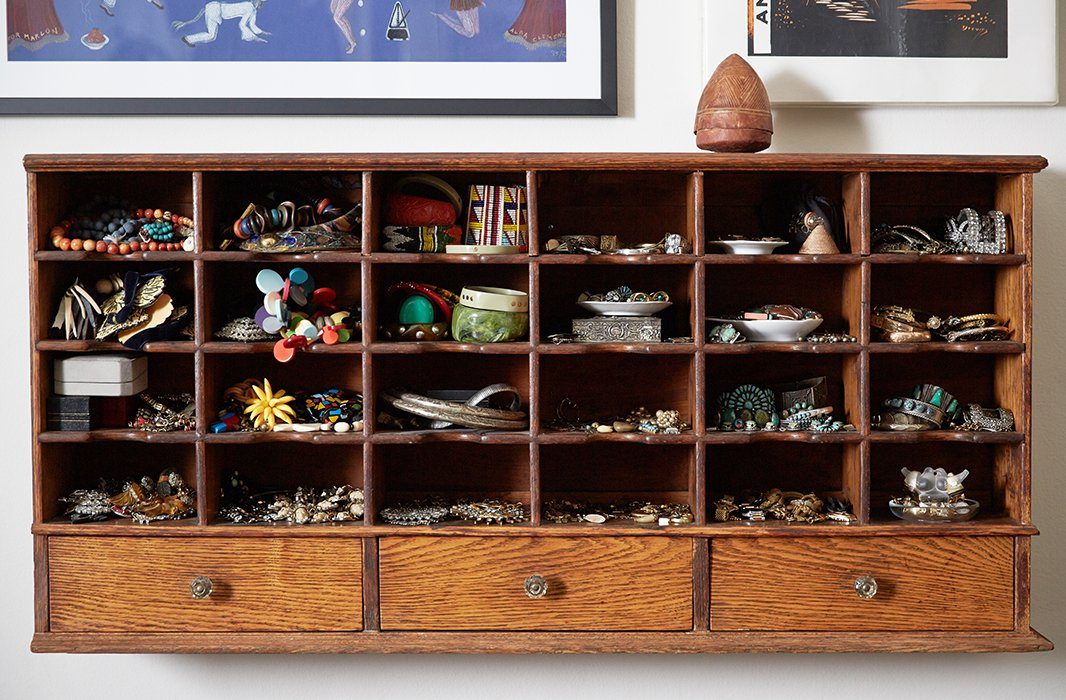 "Lisa's enviable jewelry collection is displayed in plain view on an old wooden shelf with cubbies just the right size for her necklaces and porcelain dishes of rings and bracelets. The shelf is incorporated into the couple's dining room gallery wall. ""It's my jewelry box,"" says Lisa, ""and I love having everything easily accessible."""