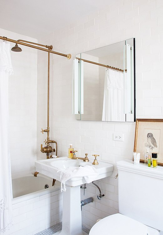 Designer Michelle Smith added unlacquered brass fixtures to her apartment's pint-size bath, leaving everything else simple and unadorned. Photo by Lesley Unruh.