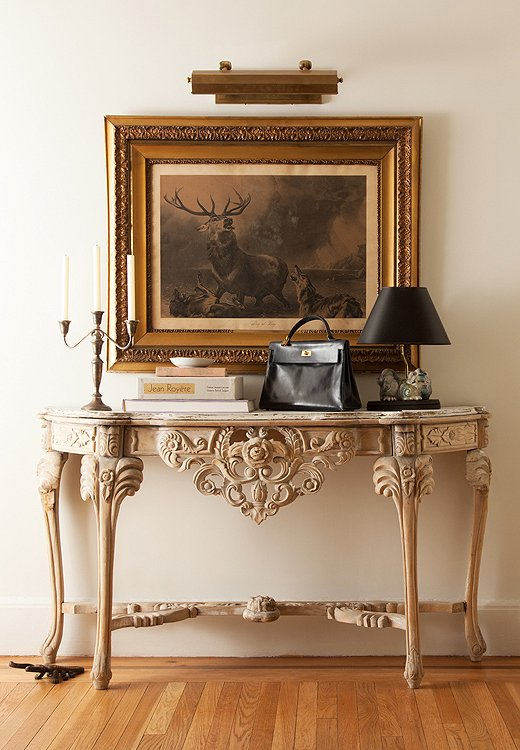 Whether you're coming or going, an unfinished carved wood table and a grandly framed flea market find create an eye-catching moment in Smith's entryway.