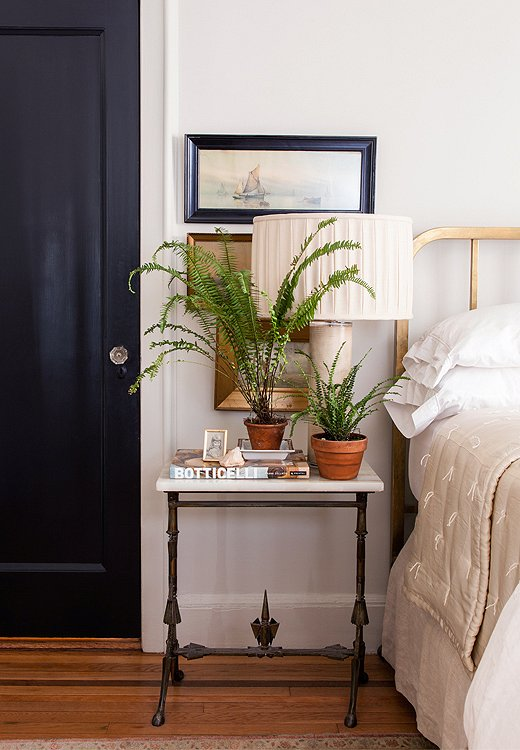 "Smith prefers to paint doors what she calls ""noncolors"" such as black or taupe rather than white. In the guest bedroom the black door adds a masculine edge to an antique brass bed and marble table."