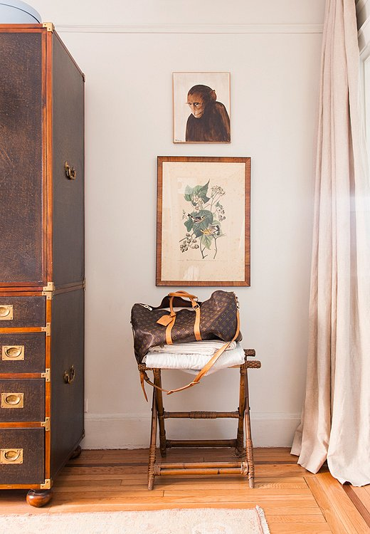 A small empty corner of the guest room becomes highly functional with the addition of a stool-cum-luggage rack. The tight palette helps make vintage finds, like the monkey painting and the Audubon print, look cohesive.