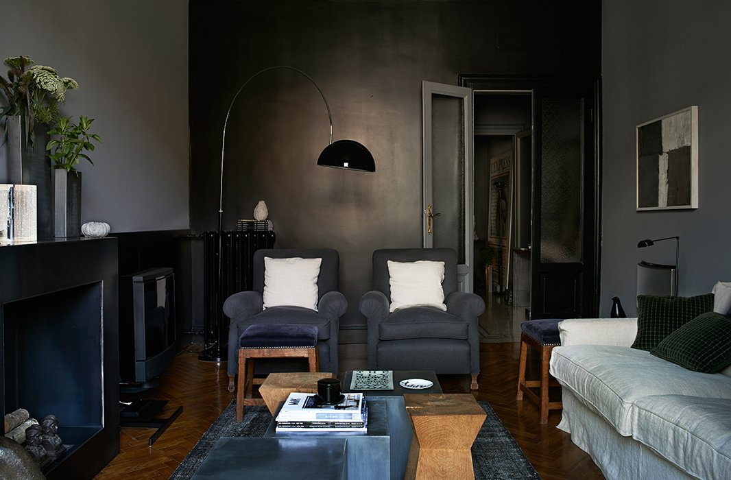 In the living room of a Milanese architect, a single black accent wall is met on either side by walls painted a dark gray. A light linen sofa and a few wood pieces balance the gray club chairs, rug, and metal coffee table.