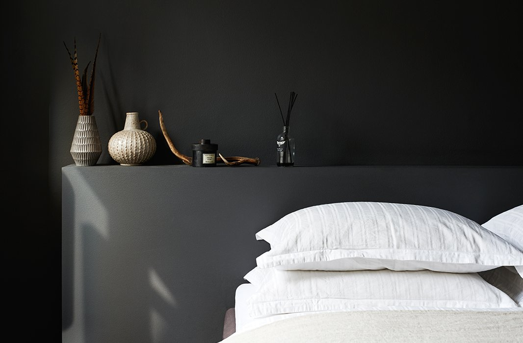 In this Copenhagen bedroom, a built-in headboard and the walls surrounding it are painted black, while the bed is a sea of textured white linens. Thecarefully chosen items above the bed add even more textural interest to the room.