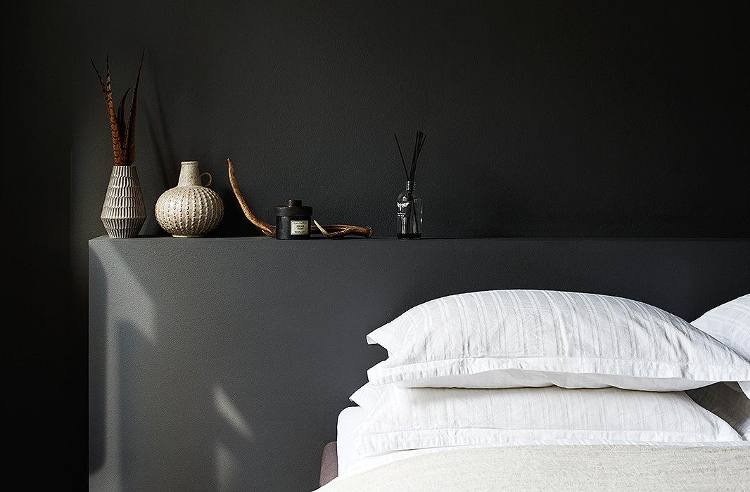 In this Copenhagen bedroom, a built-in headboard and the walls surrounding it are painted black, while the bed is a sea of textured white linens. The carefully chosen items above the bed add even more textural interest to the room.