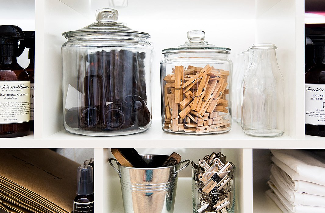 Glass containers act as both storage and a bit of stylish decor for the office shelves.