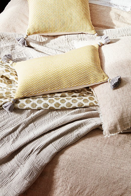 Tasseled corners and fringed edges add refinement to the organic materials. Shown above: Logan Duvet Cover and Sham in Terracotta, Harbour Matelassé Blanket in Taupe, Ella Square and Lumbar Pillows in Citrus.