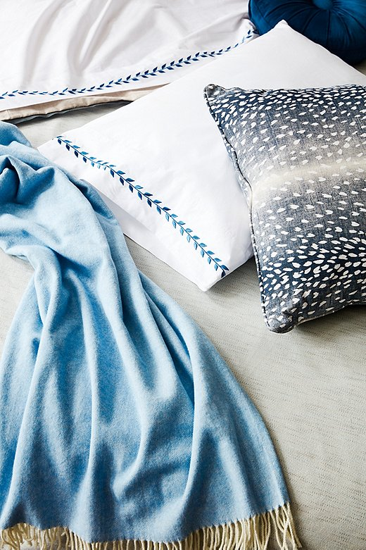 An animal-print pillow provides an unexpected pop among the more-traditional bedding. Shown above: Corbin Spa Duvet Cover, Herringbone Throw in Blue Denim, Meredith Sheet Set in Hamptons Blue, Eileen Round Pillow in Indigo, and Doeskin Pillow in Indigo/White.