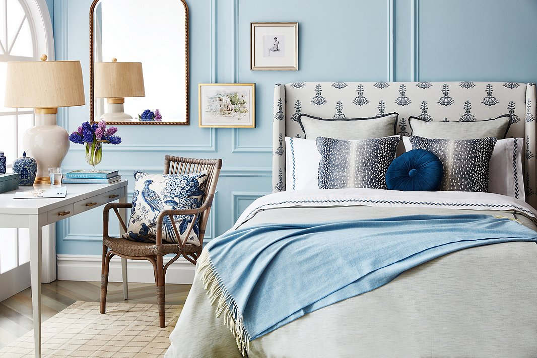 The variety of the blue hues ensures that the tight palette doesn't feel flat. Furnishings above include Cleo Seagrass Table Lamp in Cream/Gold, Piano Armchair in Taupe Gray, Floral Pheasant Pillow in Beige (on chair), Deerfield Rug, and Kelly Headboard in Lila Block Print (also available as a bed).