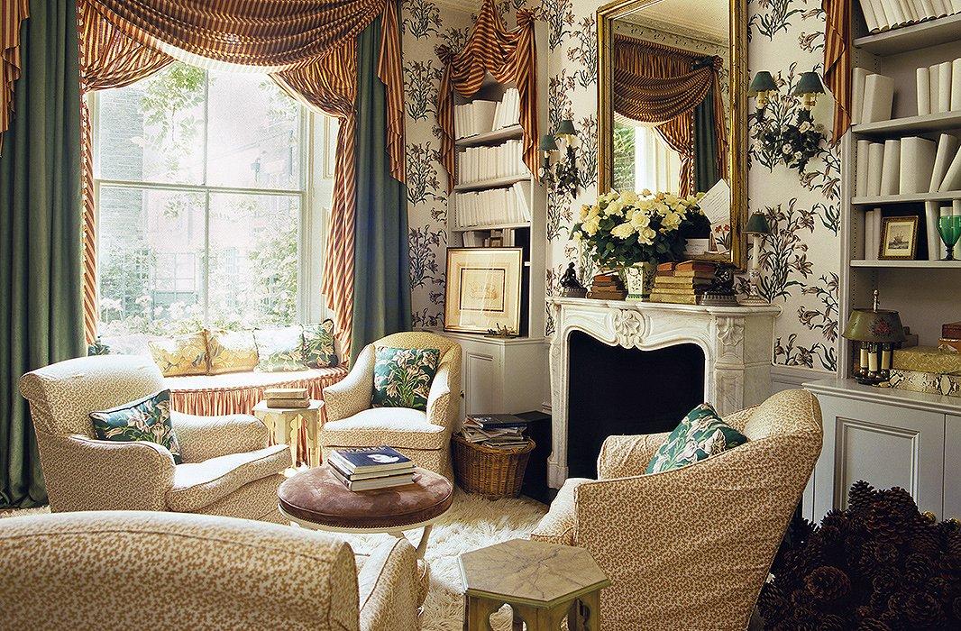 Two sets of armchairs, made to look identical with a pale patterned fabric and a fluffy rug, create a space that's grand but cozy.