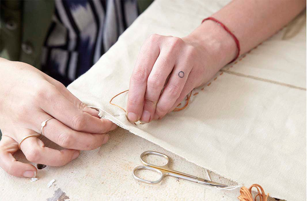 Nadia applying hand-stitched details to a piece of fabric.