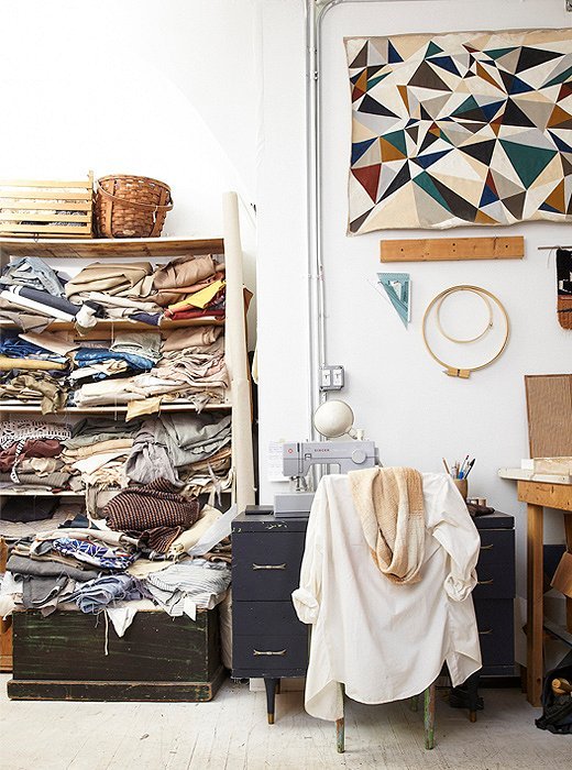 Some of the organic fabrics used for their signature textiles are stored in an open cabinet.