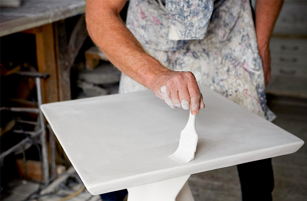 Layers of plaster are painstakingly applied with a paintbrush.
