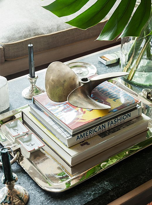 In Thom Filicia's elegant lake house, he layers a lovely silver tray under books and nautical accents on his coffee table.