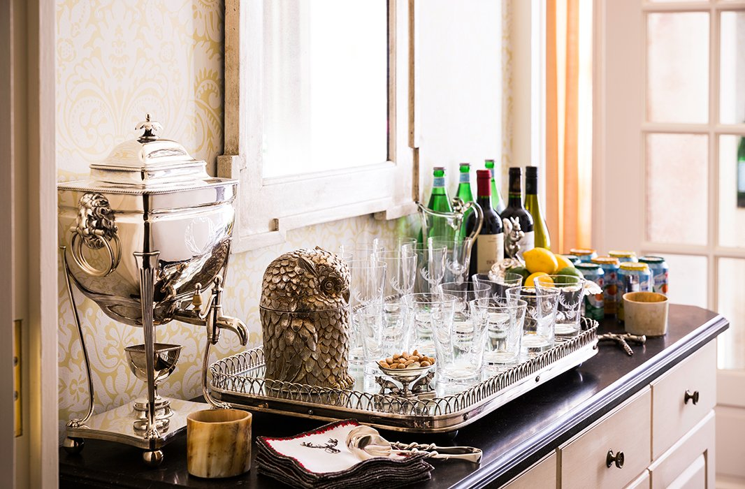 "Just off the kitchen, a self-serve bar set with an antique tray, thin glassware, and a silver coffee service that belonged to Alessandra's grandmother helps relieve bartending duties. The quirky owl ice bucket is a visual pun on Alessandra's family name, which means ""little owl."""